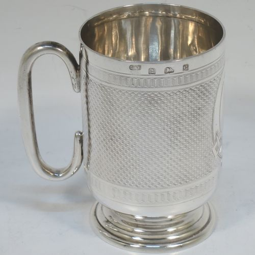 A handsome Antique Edwardian Sterling Silver christening mug, having a round straight sided body with tucked under belly, with machine-engraved decoration surrounding a vacant belt-buckle cartouche, a plain loop side-handle, and sitting on a pedestal foot. Made by Deakin and Francis of Birmingham in 1904. The dimensions of this fine hand-made antique silver christening mug are height 9 cms (3.5 inches), length 8.5 cms (3.3 inches), and it weighs approx. 93g (3 troy ounces).