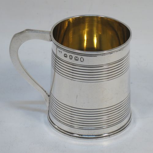 A very handsome Antique Georgian Sterling Silver christening mug, having a plain round body with two bands of hand-chased reeded decoration, an applied reeded top border, a scroll handle, a gold-gilt interior, and sitting on a flat base. Made by Peter and William Bateman of London in 1807. The dimensions of this fine hand-made antique silver christening mug are height 6.5 cms (2.5 inches), length 8 cms (3 inches), and it weighs approx. 100g (3.2 troy ounces).