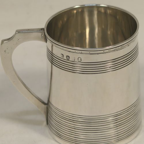 A very handsome Antique Georgian Sterling Silver christening mug, having a plain round body with two bands of hand-chased reeded decoration, an applied reeded top border, a scroll handle, and sitting on a flat base. Made by Charles Chesterman II of London in 1804. The dimensions of this fine hand-made antique silver christening mug are height 6.5 cms (2.5 inches), length 8 cms (3 inches), and it weighs approx. 90g (3 troy ounces).