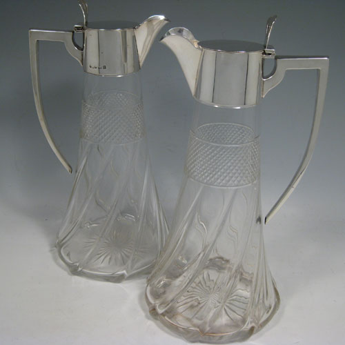 Antique Edwardian sterling silver and hand-cut crystal pair of claret jugs, having plain mounts and handles, hinged lids with pierced thumb-pieces, and Art Nouveau swirl-fluted bodies with diamond-cut bands. Made by William Hutton of Birmingham in 1905/1906. Height 26.5 cms (10.5 inches), diameter at base 13 cms (5 inches).