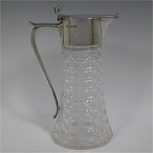 A very handsome Antique Victorian Sterling Silver and hand-cut crystal claret jug, having a plain oval mount, a hinged flat lid with scroll finial, a plain scroll handle with thumb-piece, together with a hand-cut Hobnail pattern oval body with straight tapering sides, and with a star-cut flat base. Made by William Hutton and Sons of London in 1900. The dimensions of this fine hand-made antique silver and crystal claret jug are height 27 cms (10.75 inches), and length 16.5 cms (6.5 inches).