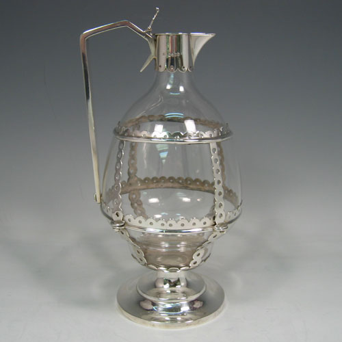 Antique Victorian sterling silver and crystal Arts & Crafts style claret jug, having a plain baluster crystal body, sitting inside a pierced frame-work that is bolted together, a plain top mount with hinged lid and thumb-piece, a plain geometrical handle, and all sitting on a pedestal foot. Made by Alexander Smith of London in 1871. Height 24 cms, length 12.5 cms (5 inches).