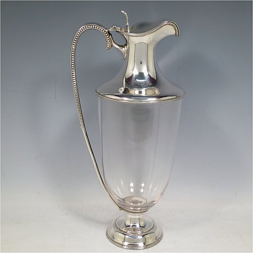 An Antique Edwardian silver-plated and hand-cut crystal claret jug, having a plain round mount with with beaded borders, a hinged lid with a hand-pierced thumb-piece, a scrolled handle with bead-work, together with a hand-cut plain round crystal body sitting on a pedestal foot. Made by Goldsmiths & Silversmiths in ca. 1900. The dimensions of this fine hand-made silver plated and crystal claret jug are height 29 cms (11.5 inches), and length 14 cms (5.5 inches).
