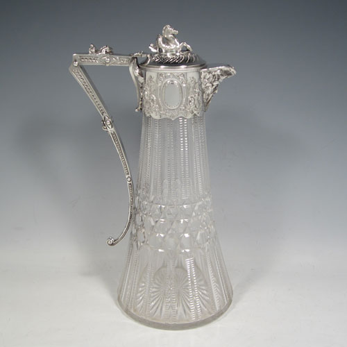 Antique Victorian silver-plated and hand-cut crystal claret jug, having a hand-chased mount with floral decoration and Bacchus face on the spout, a cast Pegasus finial, a scrolled cast handle, and a hand-cut body with geometrical work and hobnail cut. Made in ca. 1880. The dimensions of this fine hand-made silver-plated claret jug are height 29 cms (11.5 inches), length 16 cms (6.3 inches).