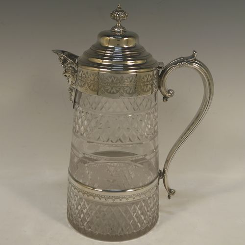 A very handsome and large Antique Victorian Silver Plated and hand-cut crystal claret jug, having a hand-engraved mount with floral decoration, a Bacchus face on the spout, a hinged stepped and domed lid with cast finial, a scroll side handle attached to a lower strengthening girdle, and a round hand-cut straight-sided body with a single band of hand-engraved frosted cut work in a grapevine pattern with two bands of hobnail pattern above and below, all sitting on a flat base with a star-cut. Made in ca.1880. The dimensions of this fine hand-made antique silver-plated and crystal claret jug are height 29 cms (11.5 inches), length 20 cms (8 inches), and diameter at the base is 13 cms (5 inches).