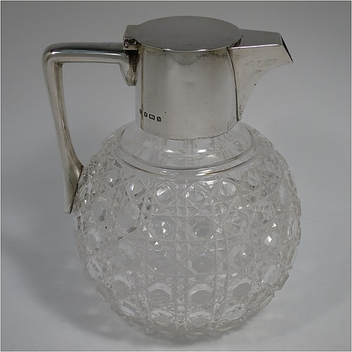 An Antique Victorian Sterling Silver and hand-cut crystal claret jug, having a plain round mount, a hinged flat lid, a plain flat-topped handle, together with a hand-cut Hobnail pattern spherical body, and with a star-cut flat base. Made by Heath and Middleton of Birmingham in 1901. The dimensions of this fine hand-made antique silver and crystal claret jug are height 16.5 cms (6.5 inches), and length 13 cms (5 inches). Please note that there are a couple of small dents in the silver mount.