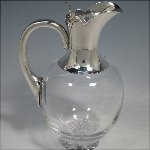 An Antique Victorian Sterling Silver and hand-cut crystal claret jug, having a plain round mount with hand-cut and applied lobed borders, a flat oval lid with a hand-cut thumb-piece, a plain looped handle, together with a hand-cut round and bellied crystal body with star-cut base. Made by William Gibson & John Langman of London in 1896. The dimensions of this fine hand-made antique silver and crystal claret jug are height 20 cms (8 inches), and length 15 cms (6 inches).
