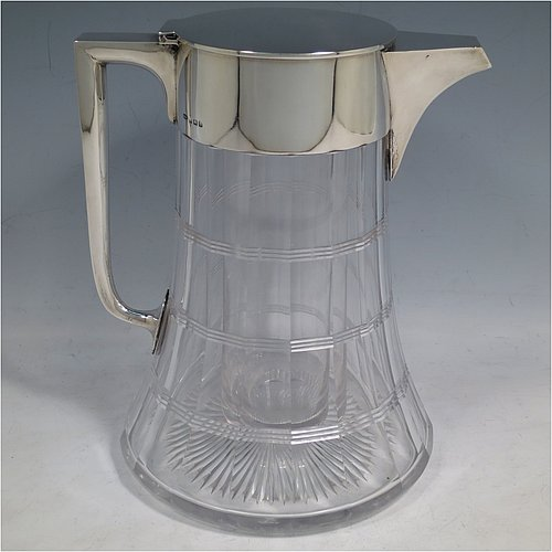 An Antique Sterling Silver and hand-cut crystal lemonade / pimms jug, having a plain round mount, with a hinged lid and a plain handle and spout, together with an original internal glass tube for crushed ice (with silver hinged handle and lift-off lid), a hand-cut panelled crystal body with bands of reeded decoration, and sitting on a flat star-cut base. Made by John Grinsell & Sons, of Birmingham in 1911. The dimensions of this fine hand-made antique silver and crystal lemonade jug are height 21 cms (8.25 inches), length 18 cms (7 inches), and diameter at base 16 cms (6.25 inches).