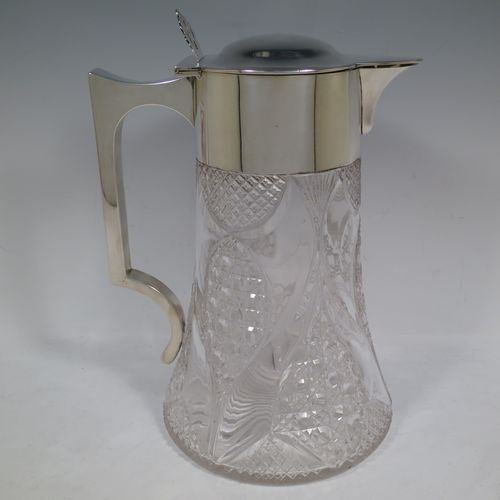 A very handsome and large Antique Victorian Sterling Silver and hand-cut crystal lemonade or pimms jug, having a plain round mount, a hinged lid with a pierced thumb-piece, a plain square cross-section handle, a sparrow-beak style spout, together with an original internal glass tube for crushed ice (with silver  handle and bayonet-fit lift-off lid), a hand-cut crystal body with lobes of hobnail-cut decoration, and all sitting on a flat star-cut base. Made by Streeter and Co. Ltd., of London in 1899. The dimensions of this fine hand-made antique silver and crystal pimms or lemonade jug are height 28 cms (11 inches), length 21 cms (8.25 inches), and diameter at base 17 cms (6.75 inches).