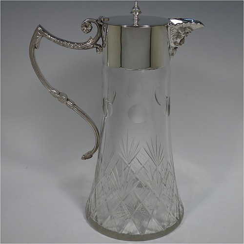 An Antique Victorian Silver-Plated and hand-cut crystal claret jug, having a plain round mount with a Bacchus face spout, a hinged flat lid with cast bell-shaped finial, a scrolled cast handle with anthemion leaf decoration, and a hand-cut crystal body, all sitting on a flat base with star-cut bottom. Made in ca. 1880. The dimensions of this fine hand-made antique silver-plated claret jug are height 28 cms (10.25 inches), length 19 cms (7.5 inches).