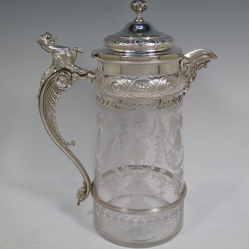 A beautiful and large Antique Victorian Silver Plated and hand-cut crystal claret jug, having a hand-chased mount with floral and bead decoration, a cast Wyvern motif spout, a hinged lid with floral chasing and a cast finial, a cast griffon scroll handle attached to a retaining ring, together with a hand-cut crystal body with frosted cut swags and lillies pattern. Made in circa 1880. The dimensions of this fine hand-made antique silver-plated and crystal claret jug are height 29 cms (11.5 inches), and length 22 cms (8.75 inches).