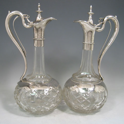 Antique Victorian 800 standard silver pair of claret jugs made in ca. 1880. With unusual mechanical opening lids. Please note that one has a beaded band around the base to indicate red wine, and the other has this band missing to indicate white wine. Height 32 cms, diameter of base 14 cms.