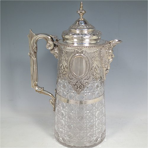 An Antique Victorian Sterling Silver and hand-cut crystal claret jug, having a hand-chased mount with floral decoration, oval vacant cartouches either side, a Bacchus face spout, a hinged lid with floral chasing and a cast finial, a cast scroll handle attached to a retaining ring, together with a hand-cut crystal body with hobnail-cut pattern. Made by Charles Boyton of London in 1882. The dimensions of this fine hand-made antique silver and crystal claret jug are height 29 cms (11.5 inches), and length 19 cms (7.5 inches).