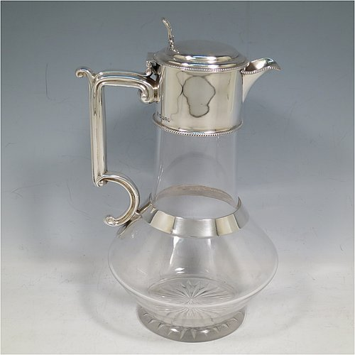 An Antique Victorian Sterling Silver and hand-cut crystal claret jug, having a plain round mount with applied bead-edge borders, a stepped domed lid with a hand-pierced finial, a scroll handle attached to a plain round security ring, together with a hand-cut round and bellied crystal body with star-cut base. Made by Walter & Charles Sissons of Sheffield in 1885. The dimensions of this fine hand-made antique silver and crystal claret jug are height 24 cms (9.5 inches), and length 15 cms (6 inches).