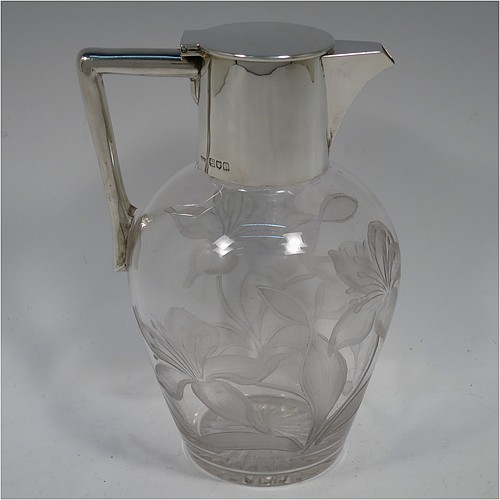 A very beautiful Antique Edwardian Sterling Silver and hand-cut crystal claret jug, having a plain round straight-sided mount, a hinged flat lid, an angular side-handle, and a hand frosted-cut body with lilly and leaf decoration, all sitting on a flat base with star-cut bottom. Made by John Grinsell and Co., in 1904. The dimensions of this fine hand-made antique silver and crystal claret jug are height 19 cms (7.5 inches), and length 13 cms (5 inches).