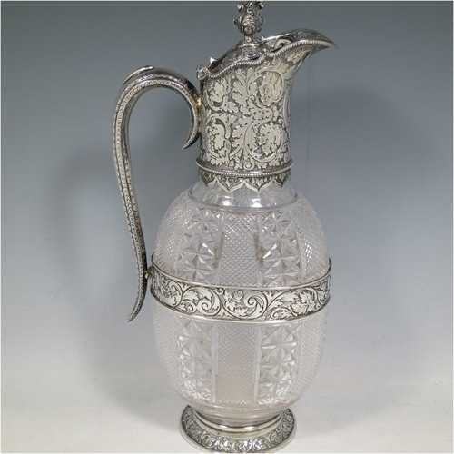 An Antique Victorian Sterling Silver and hand-cut crystal claret jug, having a hand-chased mount with floral decoration and a wavey bead-edged border, a hinged lid with cast floral finial, a hand-chased and engraved scroll handle attached to a hand-pierced floral band, together with an oval cross-section hand-cut Webb crystal body with star-cut panels, all sitting on a matching collet foot. Made by Gibson & Langland of London in 1890. The dimensions of this fine hand-made antique silver and crystal claret jug are height 31 cms (12.25 inches), and length 15 cms (6 inches).