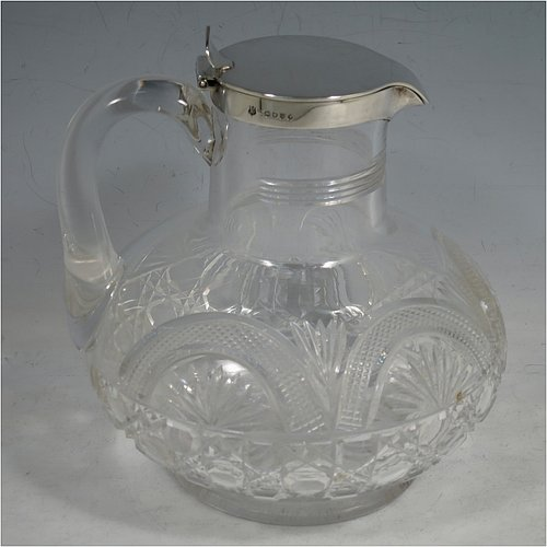 An Antique Victorian Sterling Silver and hand-cut crystal claret jug, having a plain round mount, a flat hinged lid with thumb-piece and spout, a plain crystal loop handle, together with a hand-cut round and bellied crystal body sitting on a collet foot. Made by Finlay & Taylor of London in 1888. The dimensions of this fine hand-made antique silver and crystal claret jug are height 16 cms (6.25 inches), and length 15 cms (6 inches).