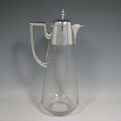 Antique Victorian sterling silver and hand-cut crystal claret jug, having a plain mount, a loop handle with flat top, a hinged lid with urn-shaped finial, a sparrow-beak spout, and a very plain straight-sided crystal body with tapering sides. Made by Martin and Hall of Sheffield in 1881. Height 30.5 cms (12 inches), diameter at base 11.5 cms (4.5 inches).