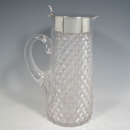 Antique Victorian sterling silver and hand-cut crystal lemonade / pimms jug, having a plain round mount, with a hinged lid and hand-pierced thumb-piece, together with an orignal internal glass tube for crushed ice (with silver hinged handle and lift-off lid), and hand-cut crystal body with loop handle. Made by John Grinsell & Sons, of London in 1894. The dimensions of this fine hand-made silver and crystal lemonade jug are height 328 cms (11 inches), and length 17 cms (6.75 inches).