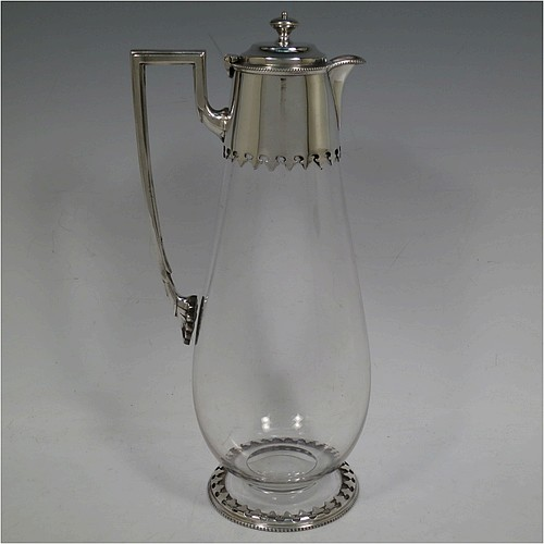 A very handsome Antique Victorian Silver Plated and hand-cut crystal claret jug, having a plain round mount with a bead-work border and hand-cut fleur-de-lis decoration, a hinged stepped lid with cast finial, a plain angular handle and a sparrow-beak style spout, together with a hand-cut crystal body with tapering sides and tucked under belly, and sitting on a collet foot with a matching bead and hand-cut cover. Made by William Hutton and Sons of Sheffield in ca. 1890. The dimensions of this fine hand-made antique silver-plated and crystal claret jug are height 28.5 cms (11.25 inches), and length 12.5 cms (5 inches).