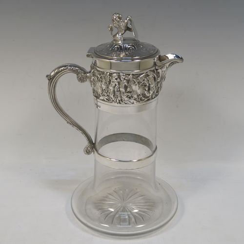 A very handsome Antique Victorian Silver Plated and hand-cut crystal claret jug, having an ornate  Bacchus style round mount with hand-chased figural work, a cast side handle with a plain round security ring, a hinged lid with a cast rampant lion and shield finial, together with a hand-cut crystal round body with straight sides and a tucked under belly above a flat star-cut base. Made by Hukin and Heath  of Sheffield in ca. 1880. The dimensions of this fine hand-made antique silver-plated and crystal claret jug are height 26 cms (10.25 inches), and length 16 cms (6.3 inches).