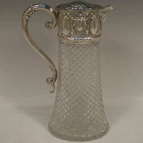 A very pretty Antique Victorian Sterling Silver and hand-cut crystal claret jug, having a hand-chased mount with floral and scroll decoration, with three oval vacant cartouches on both sides, a hinged domed lid with a gadroon border and finial, a scrolled handle with leaf work, and an oval hand-cut straight-sided body with hobnail pattern and star-cut base. Made by William Hutton of London in 1895. The dimensions of this fine hand-made antique silver and crystal claret jug are height 27 cms (10.75 inches), and length 17 cms (6.75 inches).