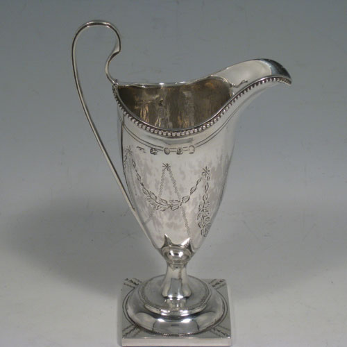 Antique Georgian sterling silver cream jug in the neoclassical Helmet style, having hand-engraved floral swags, a bead edged border, loop handle, and sitting on a square-based pedestal foot. Made in London in 1790. Height 15 cms (6 inches), length 10 cms (4 inches). Weight approx. 95g (3 troy ounces).