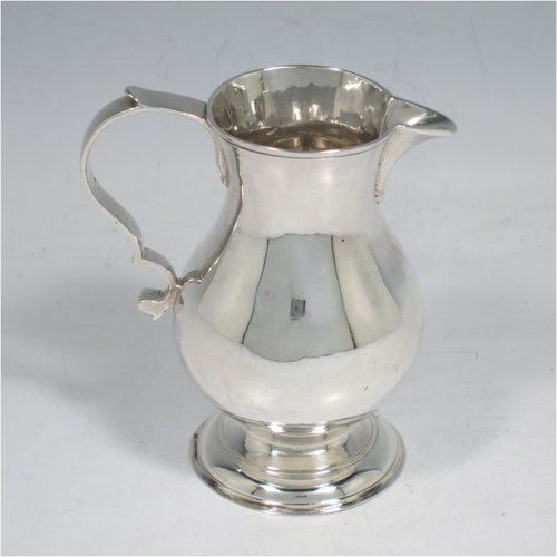 An Antique Georgian Sterling Silver cream jug, in the sparrow-beak style, having a round baluster body, scroll handle, and sitting on a collet foot. Made by George Hindmarsh of London in 1749. The dimensions of this fine hand-made antique silver cream jug are height 9 cms (3.5 inches), length 8 cms (3 inches), and it weighs approx. 82g (2.6 troy ounces).