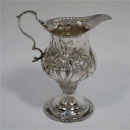 A very pretty Antique Georgian Sterling Silver cream jug, having a round bellied body with punched bead borders and hand-chased floral decoration, a scroll handle and sitting on a pedestal foot. Made by Benjamin Mountigue of London in 1780. The dimensions of this fine hand-made antique silver cream jug are height 11.5 cms (4.5 inches), length 10 cms (4 inches), and it weighs approx. 78g (2.5 troy ounces).