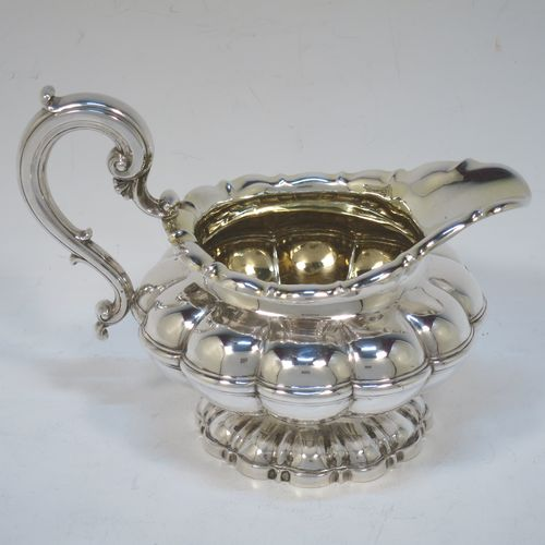 A very pretty Antique late Georgian Sterling Silver large cream jug, having a lobed round  body with hand-chased melon fluting, a scroll top border, a scroll handle with thumb-piece, a gold-gilt interior, and all sitting on a matching pedestal foot. Made by the Barnard Brothers of London in 1829. The dimensions of this fine hand-made antique silver cream jug are height 12 cms (4.75 inches), length 16 cms (6.25 inches), and it weighs approx. 233g (7.5 troy ounces).
