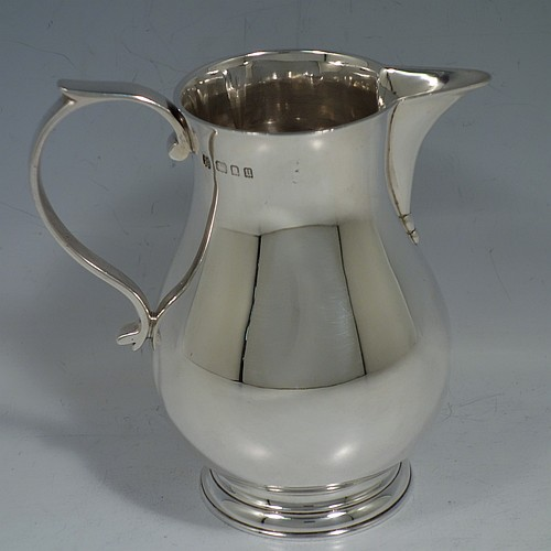 A large Sterling Silver cream jug, in the sparrow-beak style, having a plain round bellied body, a scroll handle, and sitting on a collet foot. Made by James Parker & Co., of London in 1935. The dimensions of this fine hand-made large silver Sparrow Beak cream jug are height 12 cms (4.75 inches), length 12 cms (4.75 inches), and it weighs approx. 250g (8 troy ounces).