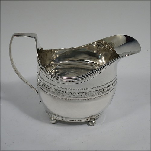 An Antique Georgian Sterling Silver cream jug, having an oval bellied body with a band of hand-engraved decoration, with an applied reeded border, a flat topped scroll handle, and sitting on four ball feet. Made by Daniel Urquart and Napthalie Hart of London in 1809. The dimensions of this fine hand-made antique silver cream jug are height 9 cms (3.5 inches), length 13 cms (5 inches), and it weighs approx. 118g (3.8 troy ounces).