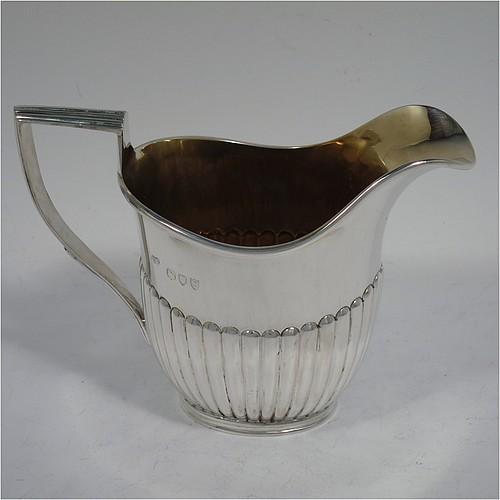 An Antique Victorian Sterling Silver cream jug in a Queen Anne style, having an oval body with hand-chased half-fluted decoration, a reeded handle and applied reeded border, a gold-gilt interior, and all sitting on a collet foot. Made by Charles Boyton of London in 1893. The dimensions of this fine hand-made antique silver cream jug are height 10 cms (4 inches), length 13.5 cms (5.3 inches), and it weighs approx. 150g (4.8 troy ounces).