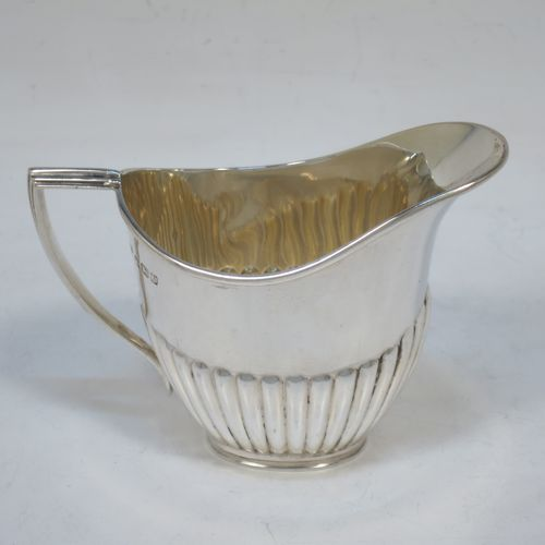 A pretty Antique Sterling Silver cream jug in a Queen Anne style, having an oval body with hand-chased half-fluted decoration, a reeded handle and applied reeded border, and all sitting on a collet foot. Made by Goldsmiths and Silversmiths of Sheffield in 1916. The dimensions of this fine hand-made antique silver cream jug are height 7.5 cms (3 inches), length 10 cms (4 inches), and it weighs approx. 55g (1.8 troy ounces).