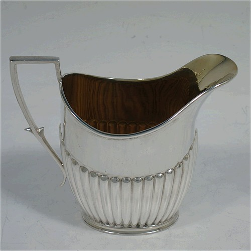 A handsome Antique Victorian Sterling Silver cream jug in a Queen Anne style, having an oval body with hand-chased half-fluted decoration, a flat topped scroll handle, reeded top and bottom border, a gold-gilt interior, and all sitting on a collet foot. Made by James Dixon and Sons of Sheffield in 1891. The dimensions of this fine hand-made antique silver cream jug are height 8 cms (3 inches), length 10 cms (4 inches), and it weighs approx. 92g (3 troy ounces).