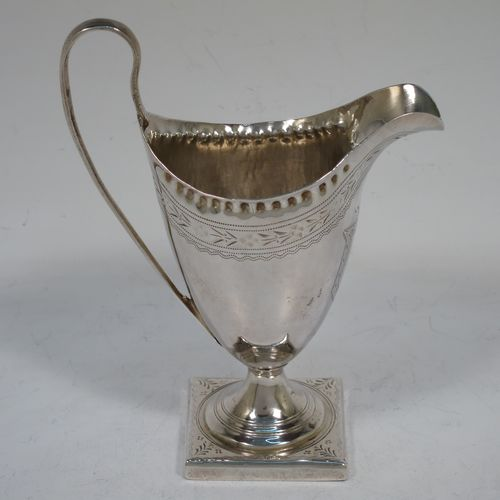 A pretty Antique Georgian Sterling Silver cream jug, having a round body with tapering sides in a Helmet style, with an upper band of floral decoration, a vacant front cartouche, a hand-punched bead border, a scroll handle, and sitting on a pedestal foot with a square base. Made by Peter and Anne Bateman of London in 1792. The dimensions of this fine hand-made antique silver cream jug are length 10 cms (4 inches), height 13 cms (5 inches), and it weighs approx. 84g (2.7 troy ounces).