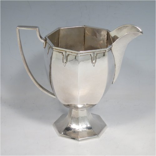 A Sterling Silver Arts & Crafts style large milk jug, having a panelled tapering body with a hand-hammered finish, an applied geometrical border, a plain handle and spout, and all sitting on a pedestal foot. Made by the Guild of Handicrafts of London in 1934. The dimensions of this fine hand-made silver cream or milk jug are height 13.5 cms (5.25 inches), length 15 cms (6 inches), and it weighs approx. 260g (8.4 troy ounces).