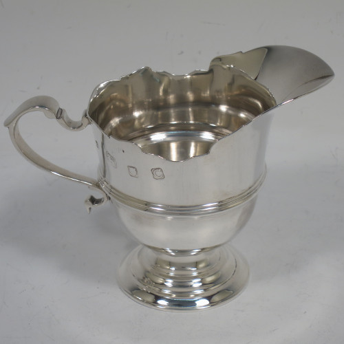 A handsome Sterling Silver cream jug in a Georgian helmet style, having a plain round bellied body, a central applied reeded band, a scroll handle and Chippendale border, and sitting on a round stepped pedestal foot. Made by Birch and Gaydon of London in 1938. The dimensions of this fine hand-made silver cream jug are length 11.5 cms (4.5 inches), height 8 cms (3.25 inches), and it weights approx. 106g (3.4 troy ounces).