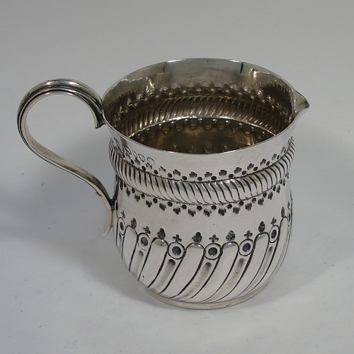 A pretty Antique Victorian Sterling Silver cream jug, having a round bellied body with hand-chased fluted and bead-work decoration, a plain reeded scroll handle opposite a sparrow-beak style spout, and sitting on a flat base. Made by John Aldwinckle and Thomas Slater of London in 1886. The dimensions of this fine hand-made antique silver cream jug are height 7 cms (2.75 inches), length 9 cms (3.5 inches), and it weighs approx. 75g (2.4 troy ounces).