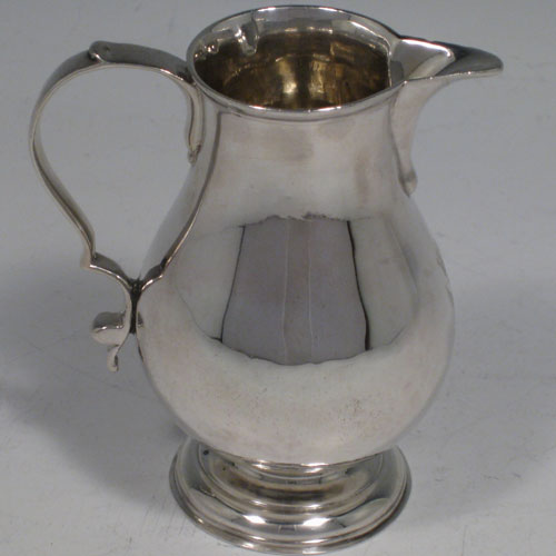 An Antique Georgian Sterling Silver cream jug, in the sparrow-beak style, having a round baluster body, scroll handle, and sitting on a collet foot. Made in the George II period and hallmarked for London in 1729. The dimensions of this fine hand-made antique silver cream jug are height 9 cms (3.5 inches), length 8 cms (3 inches), and it weighs approx. 95g (3.1 troy ounces). Please note that this item is crested.