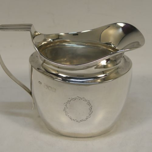 A very handsome Antique Victorian Sterling Silver cream jug, having a plain oval bellied body with a cape-style spout, a vacant laurel-leaf cartouche on one side, an applied reeded border and reeded scroll handle, and all sitting on a flat base. Made by Asher Solovitch of London in 1900. The dimensions of this fine hand-made antique silver cream jug are height 10 cms (4 inches), length 13 cms (5 inches), and it weighs approx. 140g (4.5 troy ounces).