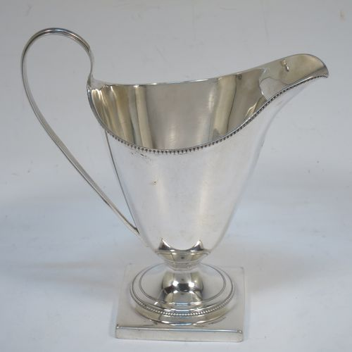 A very elegant Antique Georgian Sterling Silver cream jug, having a round body with tapering sides in a Helmet style, an applied bead-edged border, a reeded scroll handle, and sitting on a pedestal foot with a square base. Made in London in 1790. The dimensions of this fine hand-made antique silver cream jug are length 12 cms (4.75 inches), height 13 cms (5 inches), and it weighs approx. 117g (3.8 troy ounces). Please note that this item is crested.