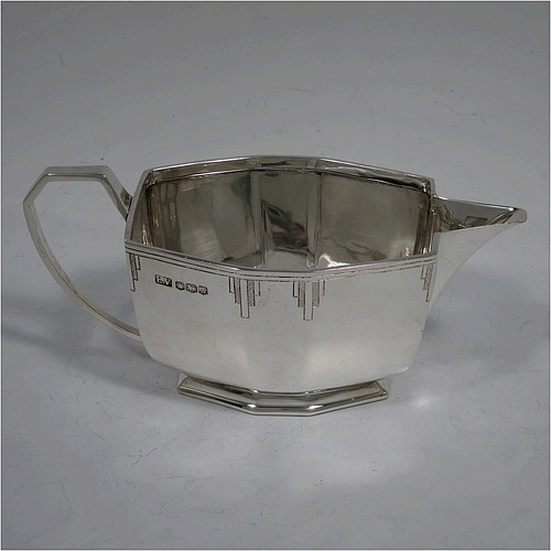 A very handsome Art Deco Sterling Silver cream jug, having a plain panelled rectangular body, a sparrow-beak spout, a cast angular handle, an applied top border with hand-engraved reeding and Deco style decals, and sitting on a collet foot. Made by Emile Viner of Sheffield in 1940. The dimensions of this fine hand-made Art Deco silver cream jug are height 7 cms (2.75 inches), length 15.5 cms (6 inches), width 7.5 cms (3 inches), and it weighs approx. 198g (6.4 troy ounces).