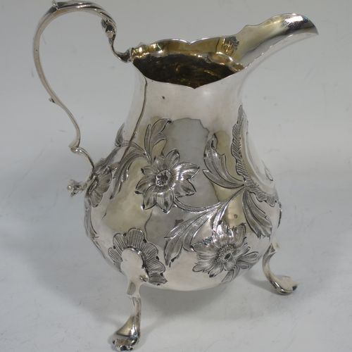 A very pretty Antique early Victorian Sterling Silver cream or milk jug having a round bellied body with hand-chased floral decoration surrounding a vacant cartouche, a scroll handle with anthemion leaf thumb-piece, a shaped border with a spout, a gold-gilt interior, and sitting on three cast trefoil feet. Made by William Hunter of London in 1845. The dimensions of this fine hand-made antique silver cream jug are height 11.5 cms (4.5 inches), length 10 cms (4 inches), and it weighs approx. 115g (3.7 troy ounces).