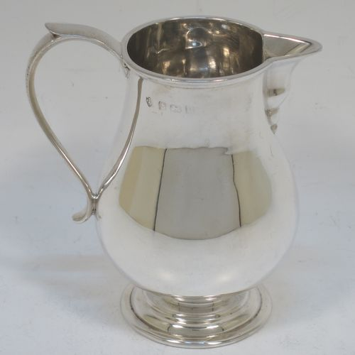 A handsome Antique Sterling Silver cream jug, in a George I Sparrow-Beak style with a plain round bellied body, an applied reeded top border, a scroll handle with plain thumb-piece and a sparrow-beak spout, and sitting on a collet foot. Made by Edward Barnard of Birmingham in 1917. The dimensions of this fine hand-made antique silver cream jug are height 9 cms (3.5 inches), length 8.5 cms (3.3 inches), and it weighs approx. 87g (2.8 troy ounces).