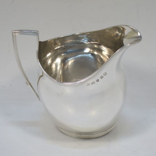 An elegant Antique Georgian Sterling Silver cream jug, having a plain oval and bellied body, an applied reeded border, a reeded handle with flat top, and sitting on a flat base. Made by Thomas Wallis II of London in 1801. The dimensions of this fine hand-made antique silver cream jug are height 10 cms (4 inches), length 10 cms (4 inches), and it weighs approx. 111g (3.6 troy ounces).