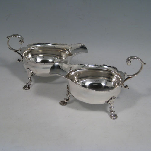 Antique Georgian George II sterling silver pair of cream boats, having wavey edged borders, cast scroll handles, and sitting on three cast hoof feet with shell shoulders. Made by Walter Brind of London in 1751. Length 13.5 cms (5.25 inches), height 8 cms (3 inches). Total weight approx. 225g (7.3 troy ounces).