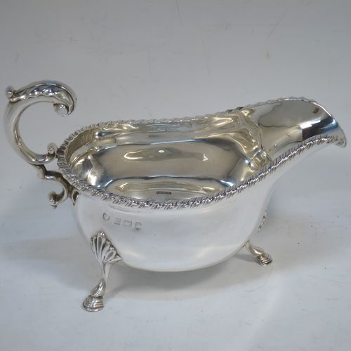 A handsome Antique Edwardian Sterling Silver sauce boat or gravy boat, having a plain bellied body, with an applied gadroon border, a cast flying scroll handle, and sitting on three cast hoof feet with shell shoulders. Made in Birmingham in 1906. The dimensions of this fine hand-made antique silver gravy or sauce boat are length 18 cms (7 inches), width 9 cms (3.5 inches), height 11 cms (4.3 inches), and it weighs approx. 233g (7.5 troy ounces).