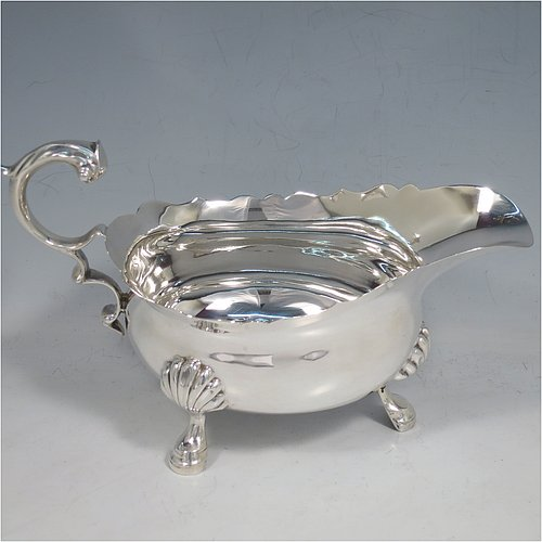 A Sterling Silver George II style large sauce or gravy boat, having a plain baluster, with a Chippendale border, a cast flying scroll handle, and sitting on three cast hoof feet with shell shoulders. Made by Edward Barnard of London in 1930. The dimensions of this fine hand-made silver sauce boat are length 20 cms (8 inches), width 9.5 cms (3.75 inches), height 11.5 cms (4.5 inches), and it weighs approx. 340g (11 troy ounces).