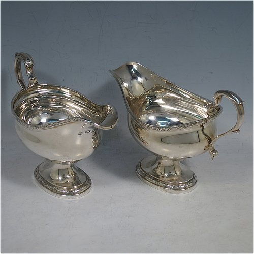 A Sterling Silver pair of sauce boats, having plain oval bellied bodies, with applied floral borders, cast scroll handles, and sitting on pedestal feet. Made by J. Parkes & Co., of London in 1938. The dimensions of this fine pair of hand-made sauce boats are length 16 cms (6.3 inches), height 11.5 cms (4.5 inches), width 8 cms (3 inches), and they weigh a total of approx. 422g (13.6 troy ounces).